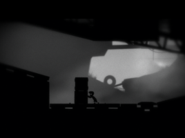 A screenshot from Limbo, showing the protagonist pushing some boxes.