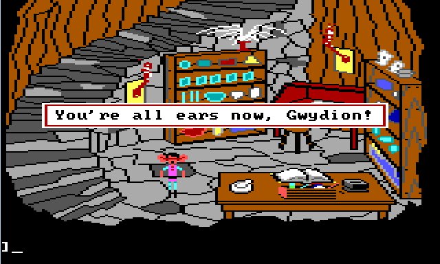 "Gwydion stands in a stone basement. Large stone stairs lead down to it. The walls are lined with shelves containing lots of beakers and jars. There is a red desk in one corner. In the foreground is a wide table with a large book on it and alchemical tools scattered around. Gwydion stands by the table. He has very large ears and looks surprised. Game text reads: ""You're all ears now, Gwydion!"""