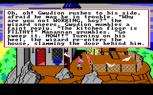 "Gwydion standing outside the house, facing Manannan, a tall wizard in black and red robes, a large white beard, and a pointed black hat. Game text reads: ""Oh, oh! Gwydion rushes to his side, afraid he may be in trouble. 'Why are you not WORKING, boy?' the wizard sneers. Gwydion mumbles a faint reply. 'The kitchen floor is FILTHY!' Manannan grumbles. 'Go sweep it. NOW!!' Turning on his heel, the wizard re-enters the house, slamming the door behind him."""