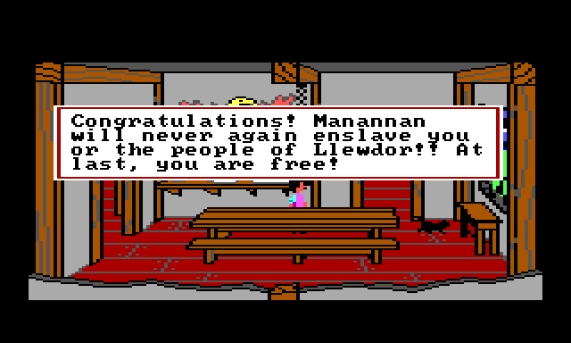 "Gwydion and a black cat in the dining room. Game text reads: ""Congratulations! Manannan will never again enslave you or the people of Llewdor! At last, you are free!"""