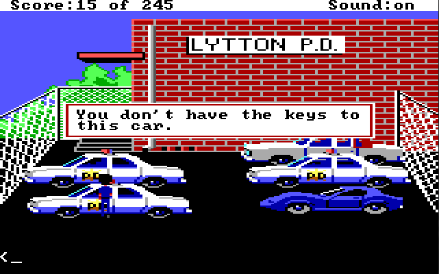 "The police station parking lot. The police station is a large red brick building in the background with a sign that says ""LYTTON PD."" There are three cop cars, a white car, and a flashy blue car parked in the lot. Sonny stands next to one of the cop cars. Game text reads, ""You don't have the keys to this car."""
