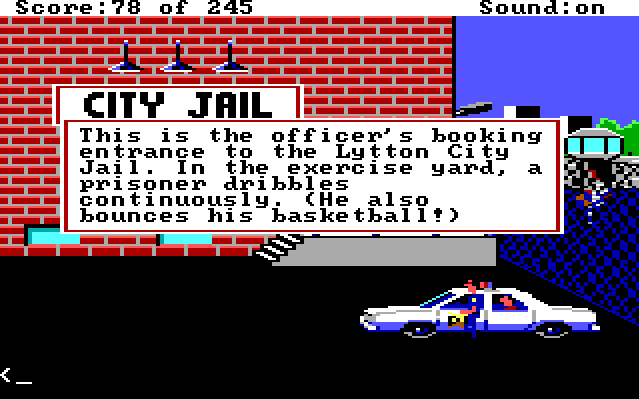 "Sonny stands in the parking lot of the jail. Behind a fence is a recreation area where a black prisoner holds a basketball. Game text reads: ""This is the officer's booking entrance to the Lytton City Jail. In the exercise yard, a prisoner dribbles continuously. (He also bounces his basketball!)"""