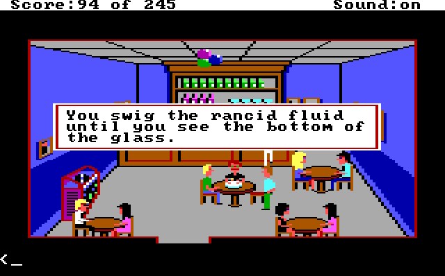 "A bar with blue walls and several tables with people at them. Cops in plainclothes are sitting around the center table, which has a birthday cake on it. A red-haired white cop with a mustache sits behind the cake. Game text reads: ""You swig the rancid fluid until you see the bottom of the glass."""