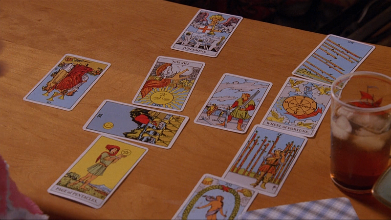 "A screen capture of Anna's spread from ""The Mountain King."" The cards are laid in a Celtic Cross on a coffee table. There is a glass of iced tea next to the spread."