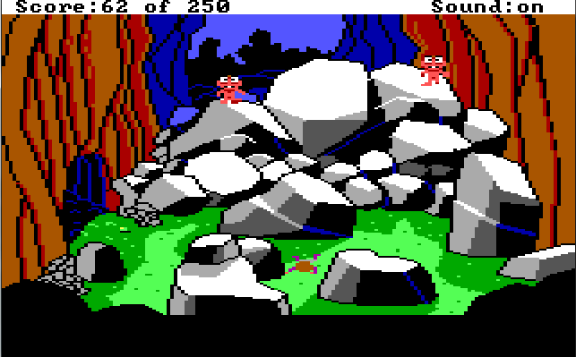 At the bottom of the ravine. There is a cave opening to the left and a large pile of boulders in the middle of the screen. Two small pink aliens with big eyes stand on the boulders. Roger lies face down on the ground in front of them.