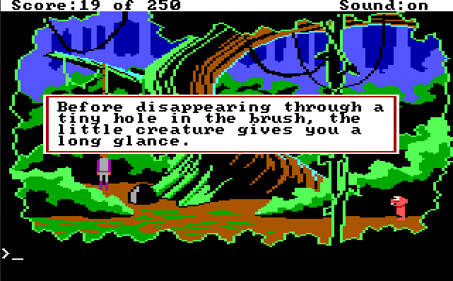 "A forest area with one large tree in the center, with vines hanging from its branches. Roger stands by the tree, and a small pink alien stands on the opposite side of the screen looking at him. Game text: ""Before disappearing through a tiny hole in the brush, the little creature gives you a long glance."""