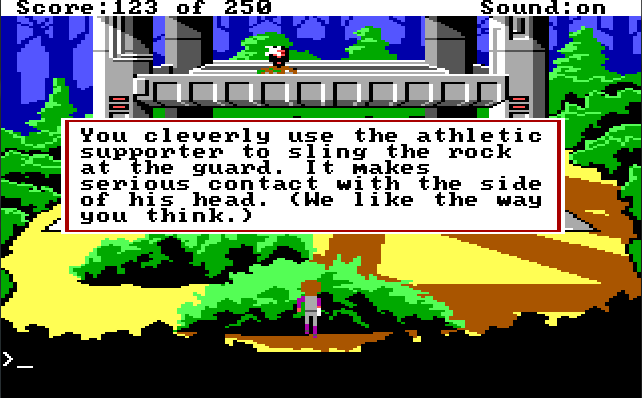 "Roger crouches behind a bush facing a metallic tower structure. A guard stands on the structure, being hit in the face with something. Game text: ""You cleverly use the athletic supporter to sling the rock at the guard. It makes serious contact with the side of his head. (We like the way you think.)"""