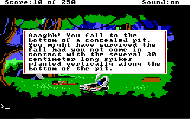 "The same forest scene, but there is now a hole in the ground on the right side of the screen. Game text: ""Aaaghh! You fall to the bottom of a concealed pit. You might have survived the fall had you not come in contact with the several 30 centimeter long spikes planted vertically along the bottom of the pit."""