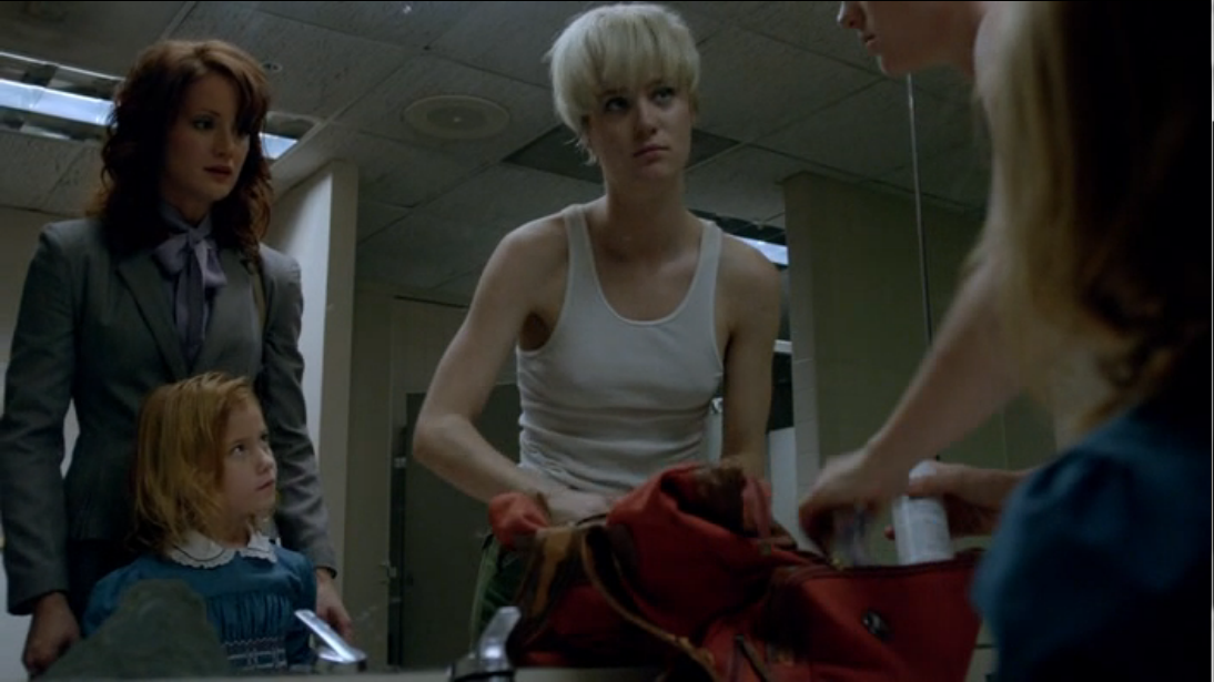 Still from Halt and Catch Fire. Two women and a little girl stand in front of a public bathroom mirror. On the left is Donna, in a prim business suit, and her young daughter. Both are staring at Cameron on the right, who is wearing only a tank top and cargo pants and is rooting through a red duffle bag on the counter.