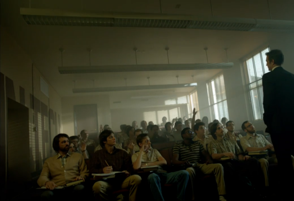 Still from Halt and Catch Fire. A man in a suit stands in front of a classroom full of men in 80's clothes. A few of the students are raising their hands.