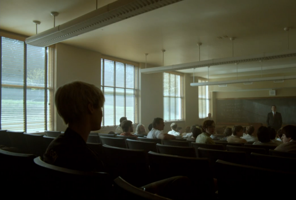 Still from Halt and Catch Fire. The classroom scene. Shot from behind Cameron where she sits in the back, with several empty rows between her and the male students.