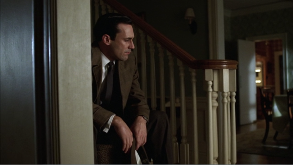 The last shot of the episode. Don sits on the stairs of his house, holding his hat. The room is dark. He is partially obscured by the wall by the stairs.