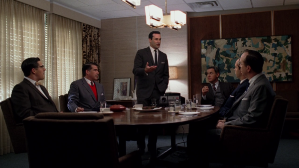 Office scene during the Kodak pitch. Don stands behind  a conference table, at which several other men are sitting. The lighting is bright and the whole scene is in focus.