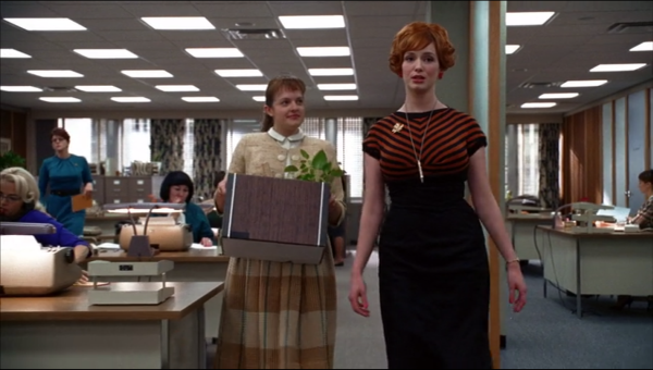 Peggy and Joan walking through the office. Peggy carries a box with a plant sticking out of it, and looks satisfied.
