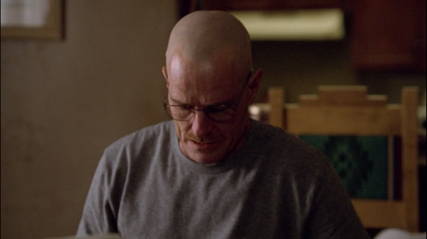 A shot from Breaking Bad. Walter White, with a shaved head, sits in his kitchen in a gray t-shirt, looking down at the table.