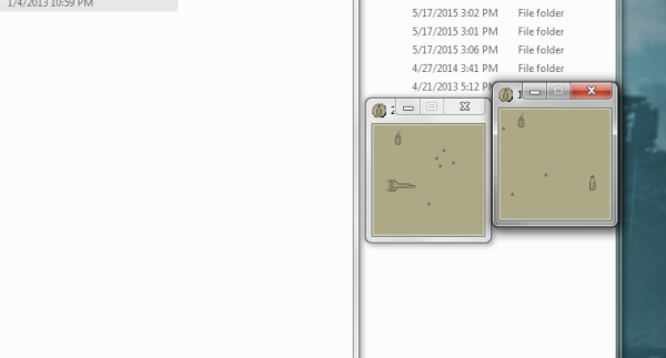 Milk! screenshot. A Windows desktop with some folders open. To the right are two small windows both showing a simple monochrome game. One window has a spaceship in it. There are milk bottles, bombs, and obstacles placed randomly around both windows.