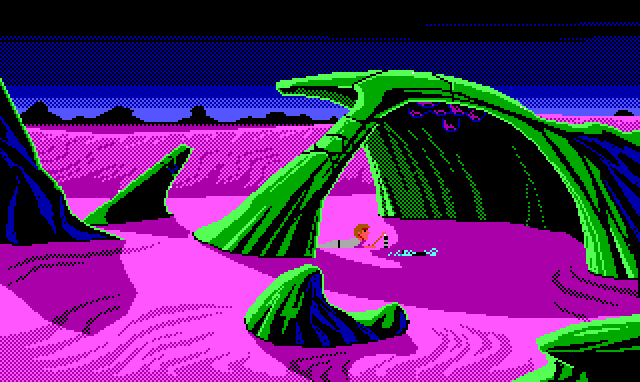 An area where curved green rock formations jut out of the purple dunes. One formation forms a wide arch, at the top of which are some dark purple blob-shaped growths. Underneath, Roger lies on his stomach and picks up some object from a metallic pile with a stick.